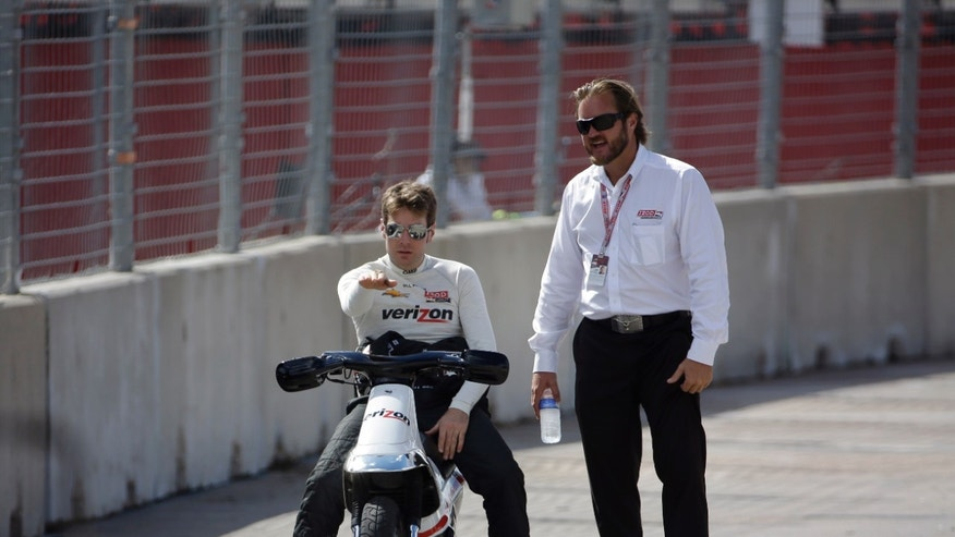 Driver Will Power, left, of Australia, points to a dip in the track as he talks with IndyCar race director beaux Barfield, right, during a delay in practice at the IndyCar Grand Prix of Houston auto race, Friday, Oct. 4, 2013, in Houston. Practice and qualifying was delayed due to a surface issue in turn one. (AP Photo/David J. Phillip)