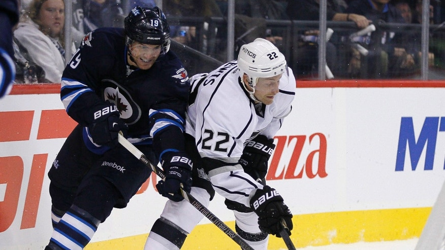 Winnipeg Jets' Jim Slater (19) and Los Angeles Kings' Trevor Lewis (22) vie for the puck in Kings territory during the second period of an NHL hockey game in Winnipeg, Manitoba, on Friday, Oct. 4, 2013. (AP Photo/The Canadian Press, John Woods)
