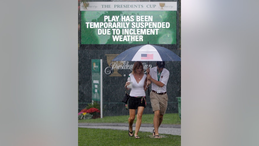 Fans brave the rain during a weather delay at the Presidents Cup golf tournament at Muirfield Village Golf Club Friday, Oct. 4, 2013, in Dublin, Ohio. (AP Photo/Jay LaPrete)