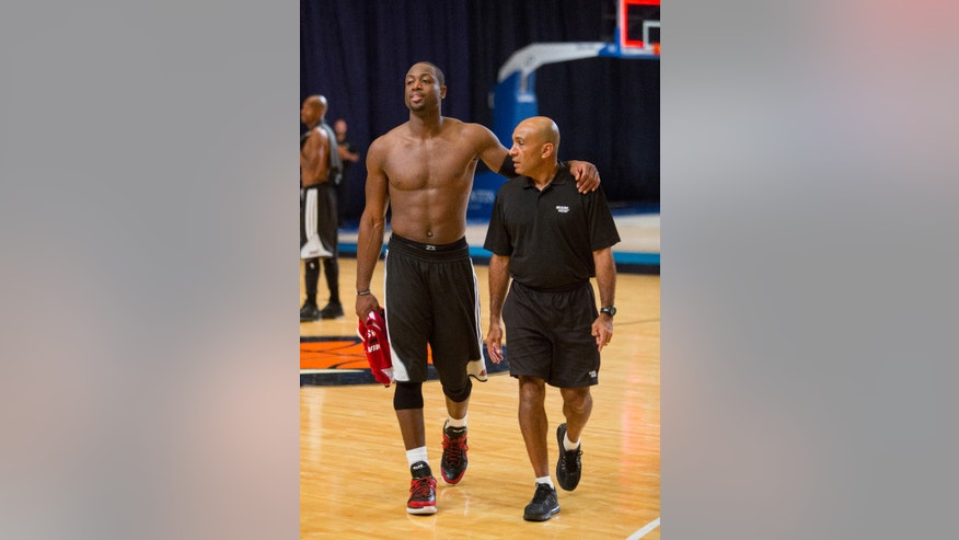 Miami Heat point guard Dwayne Wade, left, walks with the team assistant Rey Jaffet after training at the Atlantis resort on Paradise Island, Bahamas, Wednesday, Oct. 2, 2013. The two-time defending NBA champions are holding a one week training camp at the resort. (AP Photo/Bahamas Visual Services, Dante Carrer)