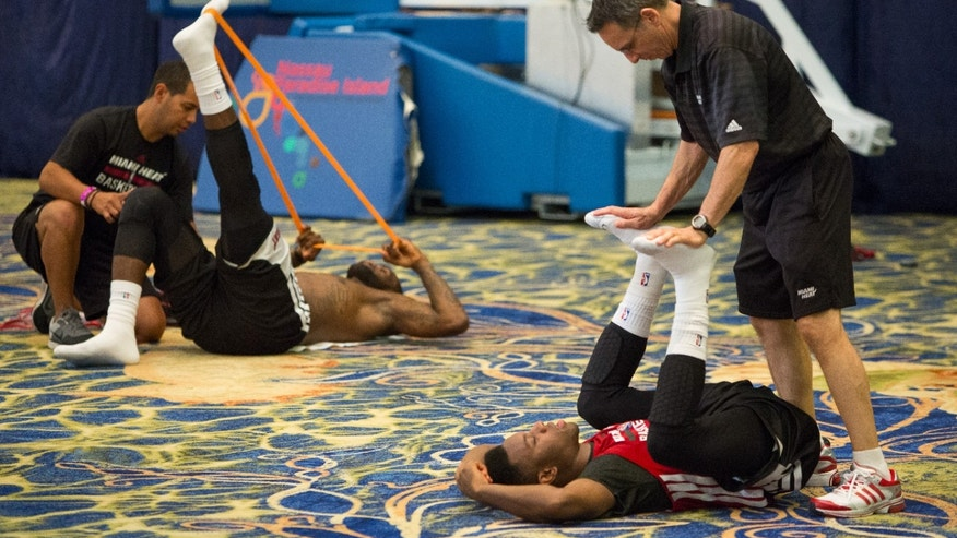 Miami Heat guard Norris Cole, right, and forward LeBron James stretch after training at the Atlantis resort on Paradise Island, Bahamas, Wednesday, Oct. 2, 2013. The two-time defending NBA champions are holding a one week training camp at the resort. (AP Photo/Bahamas Visual Services, Dante Carrer)