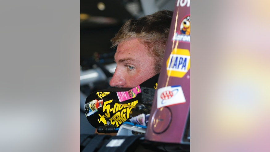Driver Clint Bowyer sits in his car during practice for Sunday's NASCAR Sprint Cup series auto race at Kansas Speedway in Kansas City, Kan., Friday, Oct. 4, 2013. (AP Photo/Orlin Wagner)