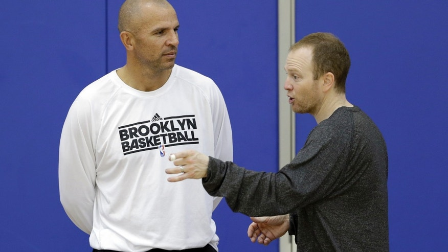 Brooklyn Nets coach Jason Kidd, left, and assistant coach Lawrence Frank talk during NBA basketball training camp at Duke University in Durham, N.C., Wednesday, Oct. 2, 2013. (AP Photo/Gerry Broome)
