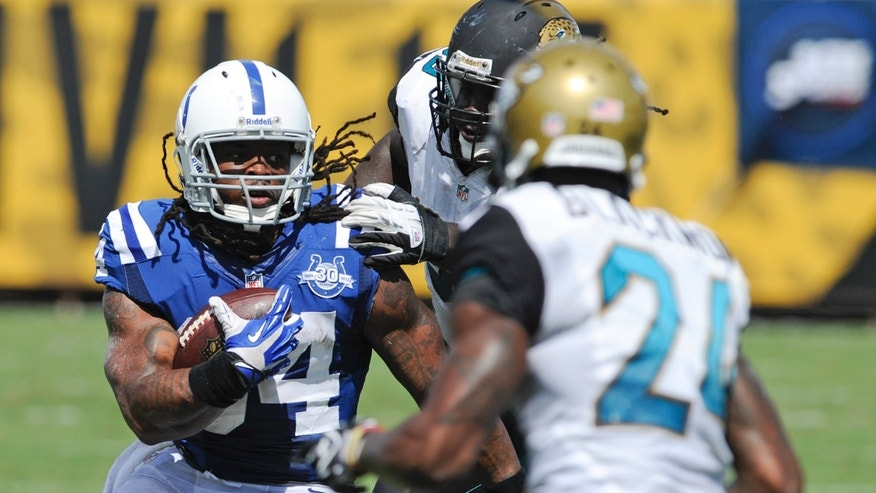 Indianapolis Colts running back Trent Richardson, left, looks for an opening around Jacksonville Jaguars cornerback Will Blackmon (24) during the first half of an NFL football game in Jacksonville, Fla., Sunday, Sept. 29, 2013.(AP Photo/Stephen Morton)