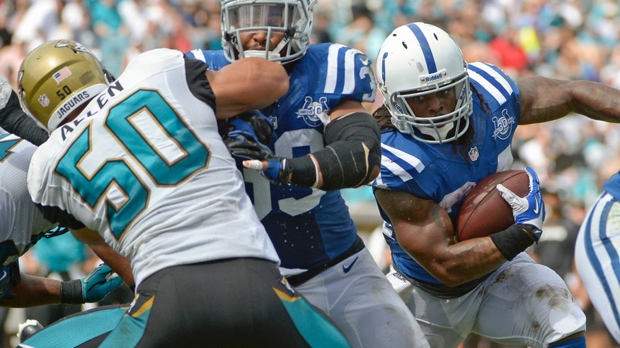 Indianapolis Colts running back Trent Richardson, right, gets a block from fullback Stanley Havili, center, as he runs past Jacksonville Jaguars outside linebacker Russell Allen (50) for a 1-yard touchdown during the first half of an NFL football game in Jacksonville, Fla., Sunday, Sept. 29, 2013.(AP Photo/Phelan M. Ebenhack)