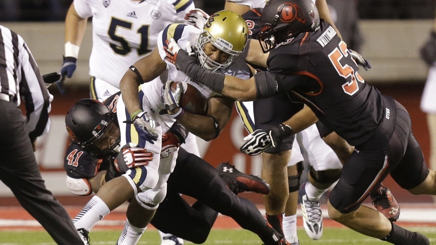 UCLA running back Jordon James, center,  carries the ball as Utah linebacker Jared Norris (41) and Utah linebacker Jason Whittingham (53) make a tackle in the second quarter during an NCAA college football game Thursday, Oct. 3, 2013, in Salt Lake City.   (AP Photo/Rick Bowmer)