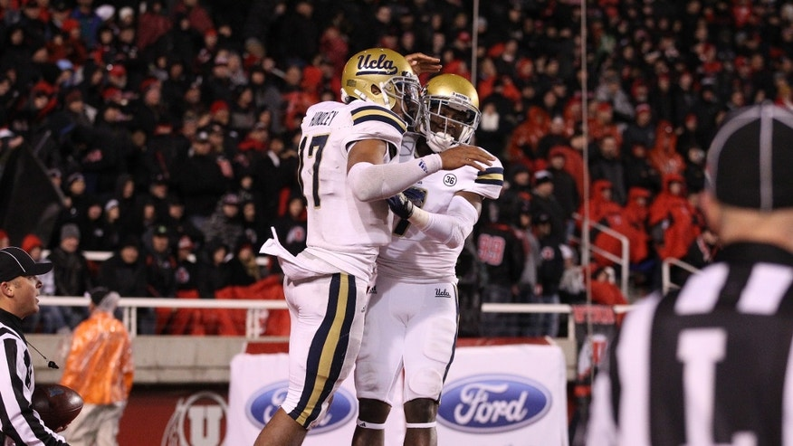 UCLA quarterback Brett Hundley (17) celebrates with teammate UCLA wide receiver Devin Fuller, right, after scoring against Utah in the fourth quarter during an NCAA college football game Thursday, Oct. 3, 2013, in Salt Lake City.  UCLA won 34-27.  (AP Photo/Rick Bowmer)