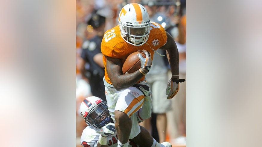 Tennessee running back Rajion Neal (20) gets past a tackle by South Alabama safety Terrell Brigham (18) while carrying the ball down the sideline in the first half of an NCAA college football game at Neyland Stadium in Knoxville, Tenn. on Saturday, Sept. 28, 2013. (AP Photo/Knoxville News Sentinel, Adam Lau)