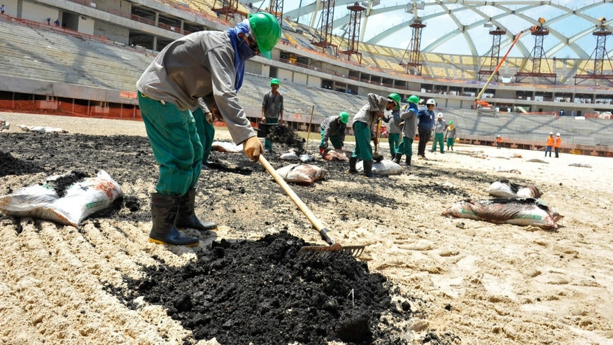 In this Sept. 2013 photo released by Portal da Copa, workers plant grass at the Arena da Amazonia stadium in Manaus, Amazonas state, Brazil. While grass was being planted here, organizers in the southern city of Curitiba looked to overturn a judge's order that halted the stadium construction because of workers' safety concerns. With less than three months to go before the December deadline established by FIFA for the delivery of the 12 World Cup soccer stadiums, Brazil is working at full steam to have all venues ready in time. (AP Photo/Alfredo Fernandes, Portal da Copa)
