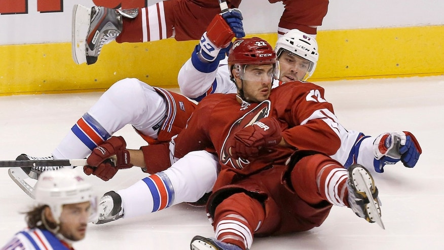 New York Rangers' Benoit Pouliot (67) takes down Phoenix Coyotes' Lucas Lessio (22) but is called for a holding penalty in the first period during an NHL hockey game on Thursday, Oct. 3, 2013, in Glendale, Ariz. (AP Photo/Ross D. Franklin)
