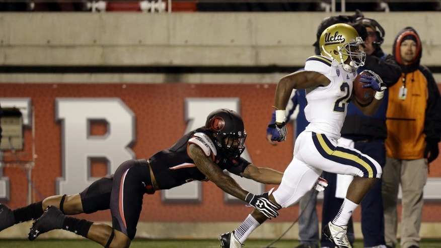 UCLA running back Paul Perkins (24) outruns Utah defensive back Keith McGill, left, in the first quarter during an NCAA college football game on Thursday, Oct. 3, 2013, in Salt Lake City. (AP Photo/Rick Bowmer)