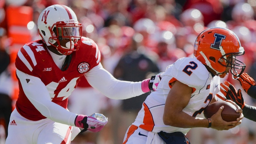 Illinois quarterback Nathan Scheelhaase (2) is pursued and later sacked by Nebraska defensive end Randy Gregory (44) in the first half of an NCAA college football game in Lincoln, Neb., Saturday, Oct. 5, 2013. (AP Photo/Nati Harnik)