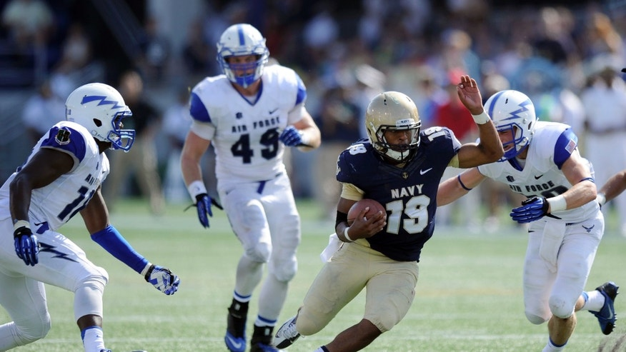 Navy quarterback Keenan Reynolds (19) weaves his way around Air Force defensive back Gavin McHenry, right, Joey Nichol (49) and Reggie Barnes, left, during the second half of an NCAA football game, Saturday, Oct. 5, 2013, in Annapolis, Md. Navy won 28-10. (AP Photo/Nick Wass)