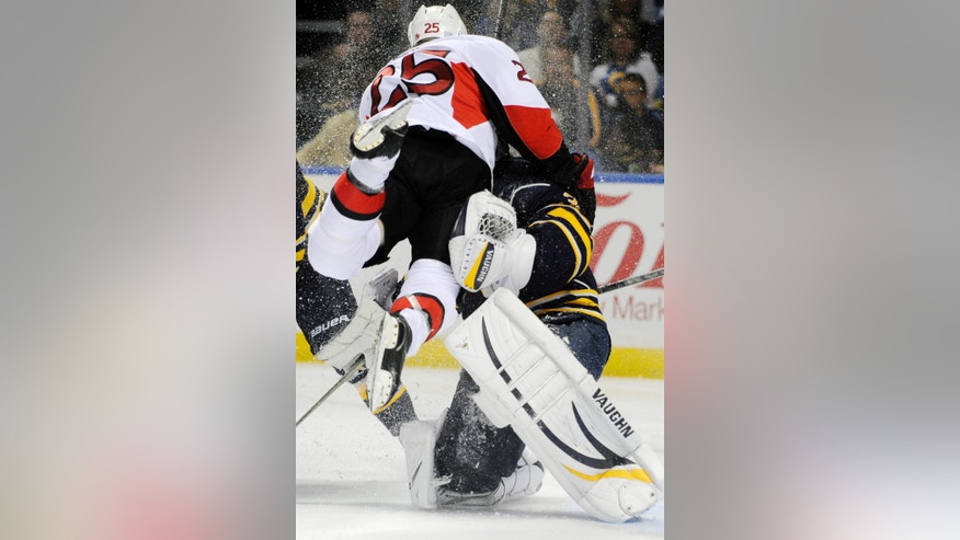 Ottawa Senators' Chris Neil (25) crashes into Buffalo Sabres goalie Ryan Miller (30) during the second period of an NHL hockey game in Buffalo, N.Y., on Friday, Oct. 4, 2013. Ottawa won 1-0. (AP Photo/Gary Wiepert)