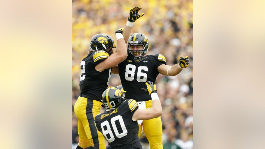 Iowa tight end C.J. Fiedorowicz (86) celebrates with teammates Ray Hamilton, left, and Henry Krieger Coble (80) after catching a 10-yard touchdown pass during the first half of an NCAA college football game against Michigan State, Saturday, Oct. 5, 2013, in Iowa City, Iowa. (AP Photo/Charlie Neibergall)