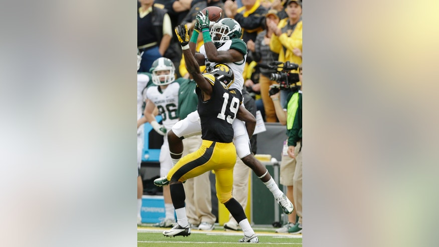Michigan State wide receiver Tony Lippett, top, catches a pass over Iowa defensive back B.J. Lowery during the first half of an NCAA college football game, Saturday, Oct. 5, 2013, in Iowa City, Iowa. (AP Photo/Charlie Neibergall)