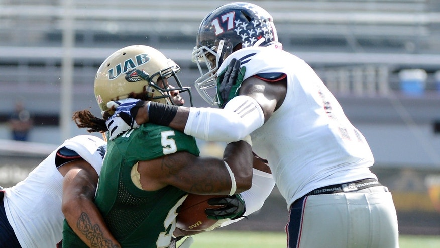 Florida Atlantic safety Damian Parms (17) wraps up UAB running back Darrin Reaves in the first quarter of a NCAA college football game at Legion Field in Birmingham, Ala., Saturday, Oct. 5, 2013.   (AP Photo/ AL.com, Mark Almond) MAGS OUT