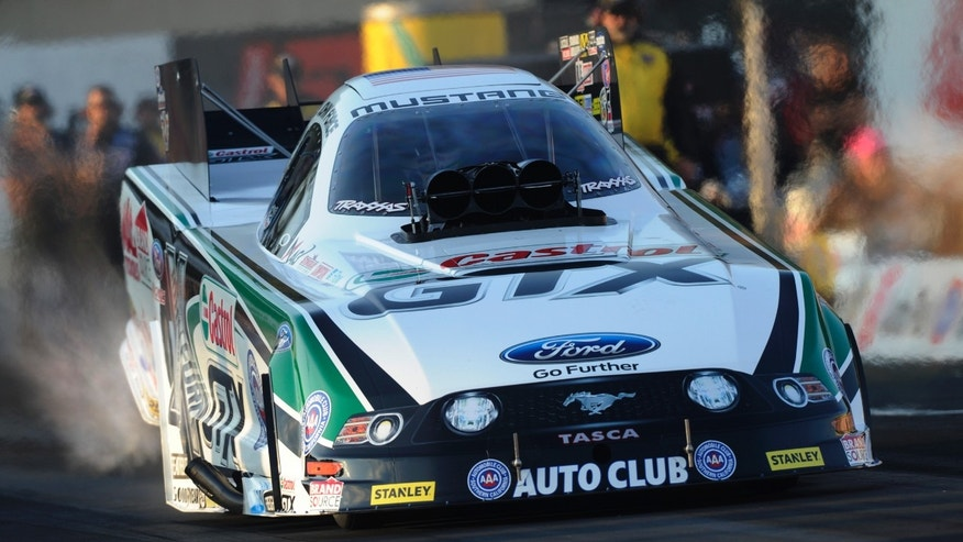 In this photo provided by NHRA, John Force makes a run in qualifying in Funny Car for the Auto-Plus NHRA Nationals drag races at Maple Grove Raceway on Friday, Oct. 4, 2013, in Mohnton, Pa. Force took the top spot in the first day of qualifying. (AP Photo/NHRA, Jerry Foss)