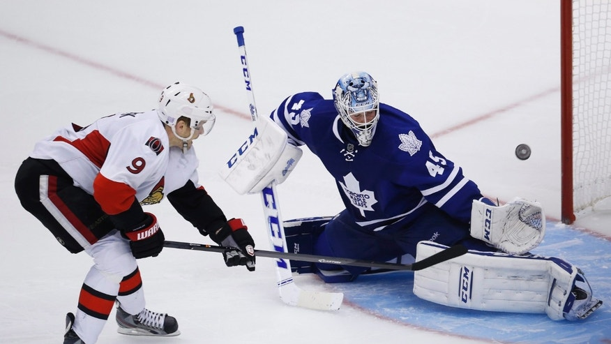 Toronto Maple Leafs goalie Jonathan Bernier, right, makes a save on Ottawa Senators Milan Michalek, left, in a shootout during an NHL hockey game in Toronto, Saturday, Oct. 5, 2013. (AP photo/The Canadian Press, Mark Blinch)