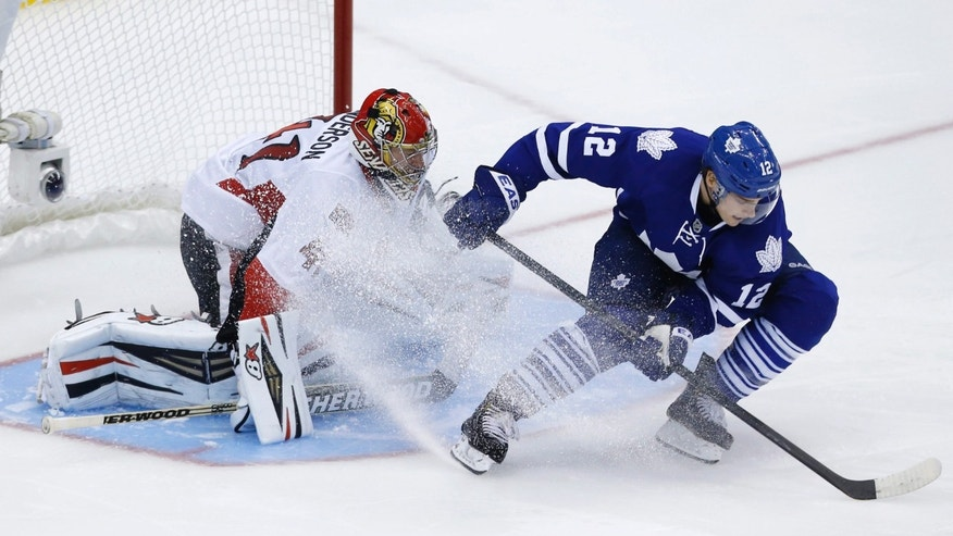 Toronto Maple Leafs' Mason Raymond, right, scores on Ottawa Senators' Craig Anderson, left, in a shootout during an NHL hockey game in Toronto, Saturday, Oct. 5, 2013. (AP photo/The Canadian Press, Mark Blinch)