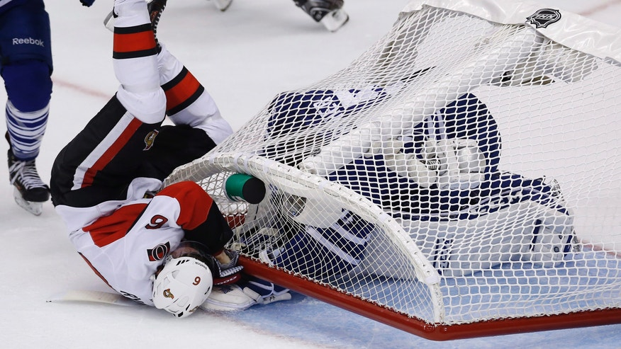 Ottawa Senators' Bobby Ryan (6) falls over with the net on top of Toronto Maple Leafs goalie Jonathan Bernier during third-period action of an NHL hockey game in Toronto, Saturday, Oct. 5, 2013. (AP photo/The Canadian Press, Mark Blinch)