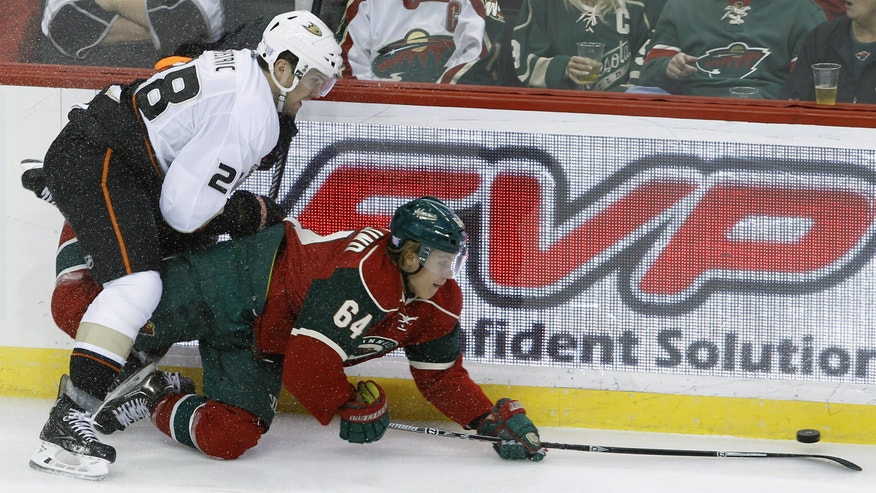 Minnesota Wild center Mikael Granlund (64), of Finland, and Anaheim Ducks defenseman Mark Fistric (28) chase the puck during the first period of an NHL hockey game in St. Paul, Minn., Saturday, Oct. 5, 2013. (AP Photo/Ann Heisenfelt)