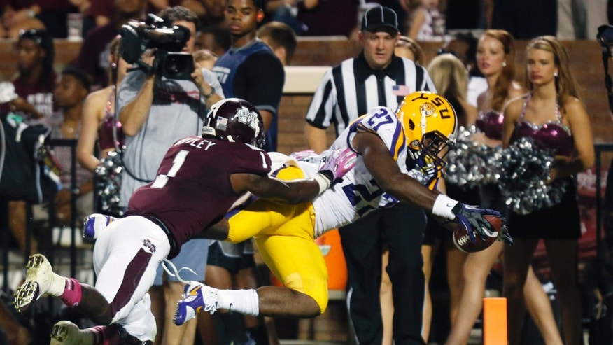 LSU running back Kenny Hilliard (27) dives past Mississippi State defensive back Nickoe Whitley (1) for a 27-yard touchdown run in the first half of their NCAA college football game in Starkville, Miss., Saturday, Oct. 5, 2013.  (AP Photo/Rogelio V. Solis)