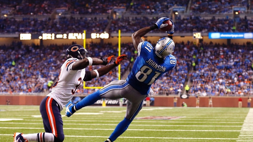 Detroit Lions wide receiver Calvin Johnson (81), defended by Chicago Bears cornerback Charles Tillman (33),  catches a two-yard touchdown from quarterback Matthew Stafford during the second quarter of an NFL football game at Ford Field in Detroit, Sunday, Sept. 29, 2013. (AP Photo/Jose Juarez)