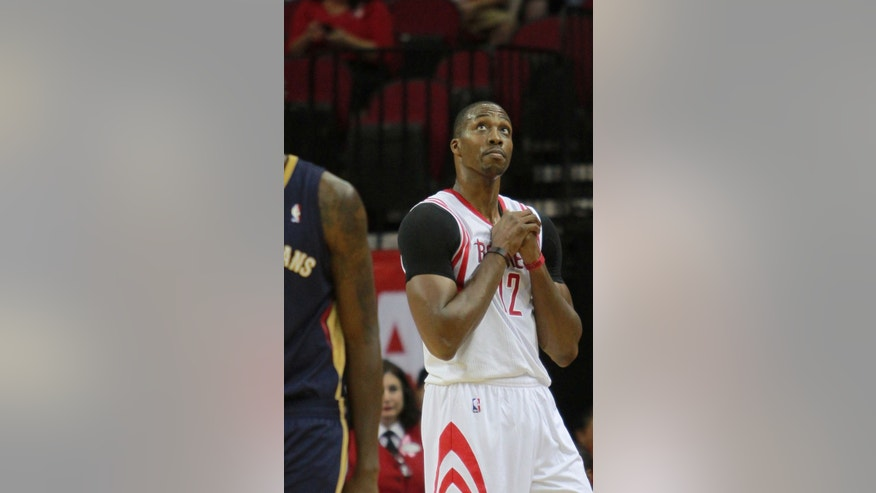 Houston Rockets center Dwight Howard looks to the scoreboard after being called for goaltending against the New Orleans Pelicans during the first half of  a preseason NBA basketball game in Houston, Saturday, Oct. 5, 2013.   (AP Photo/Richard Carson)
