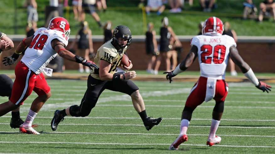 Wake Forest quarterback Tanner Price, center, scrambles as North Carolina State's Robert Caldwell (48) and Hakim Jones (20) defend in the first half of an NCAA college football game in Winston-Salem, N.C., Saturday, Oct. 5, 2013. (AP Photo/Chuck Burton)