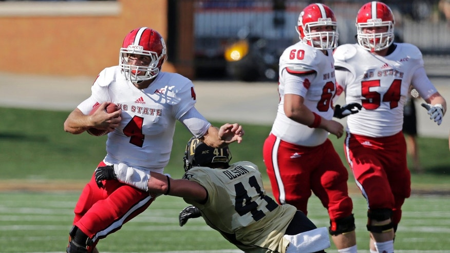North Carolina State's Pete Thomas (4) is tackled by Wake Forest's Mike Olson (41) in the first half of an NCAA college football game in Winston-Salem, N.C., Saturday, Oct. 5, 2013. (AP Photo/Chuck Burton)