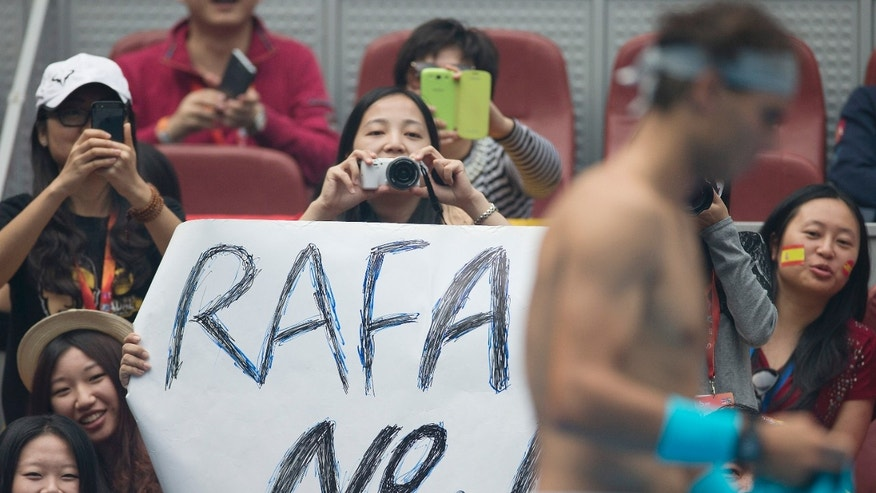 Chinese fan take pictures when Rafael Nadal of Spain changes his shirt during his semifinal match of the China Open tennis tournament against Tomas Berdych of Czech Republic at the National Tennis Stadium in Beijing, China Saturday, Oct. 5, 2013. Nadal was a break up at 4-2 in the opening set of their semifinal match when Berdych retired soon after taking an injury timeout. (AP Photo/Andy Wong)