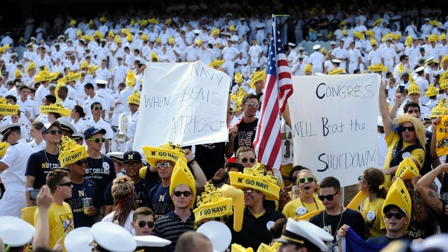 Fans display signs commenting on the government shutdown during the first half of an NCAA football game between Navy and Air Force, Saturday, Oct. 5, 2013, in Annapolis, Md. (AP Photo/Nick Wass)