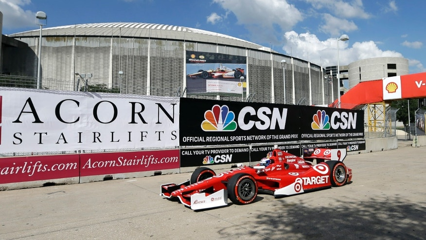 Scott Dixon, of New Zealand, passes the Houston Astrodome during the first IndyCar Grand Prix of Houston auto race, Saturday, Oct. 5, 2013, in Houston. (AP Photo/David J. Phillip)