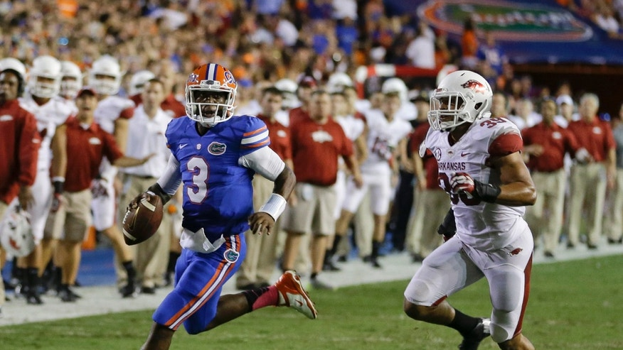Florida quarterback Tyler Murphy (3) looks for a receiver as he scrambles away from Arkansas linebacker Jarrett Lake, right, during the first half of an NCAA college football game in Gainesville, Fla., Saturday, Oct. 5, 2013.(AP Photo/John Raoux)