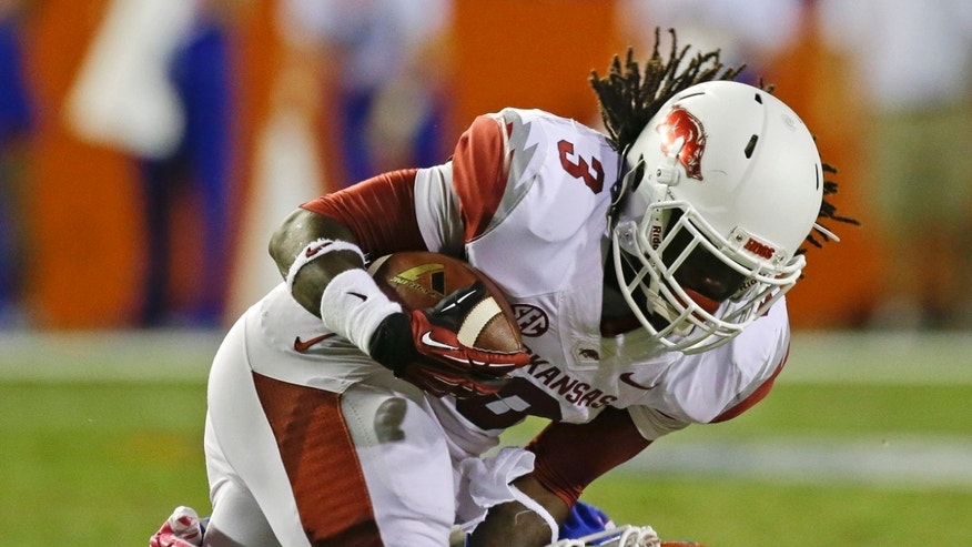 Arkansas running back Alex Collins (3) is tackled by Florida defensive back Jabari Gorman after a short gain during the first half of an NCAA college football game in Gainesville, Fla., Saturday, Oct. 5, 2013. (AP Photo/John Raoux)