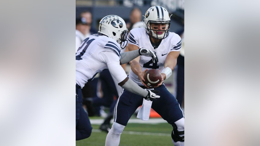 Brigham Young quarterback Taysom Hill (4) hands off to Jamaal Williams (21) during an NCAA college football game against Utah State on Friday, Oct. 4, 2013, in Logan, Utah. The Cougars won 31-7. (AP Photo/The Salt Lake Tribune, Leah Hogsten)