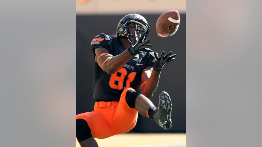 Oklahoma State wide receiver Jhajuan Seales catches a 43-yard pass from quarterback J.W. Walsh during the first half of an NCAA college football game against Kansas State in Stillwater, Okla., Saturday, Oct. 5, 2013. (AP Photo/Brody Schmidt)