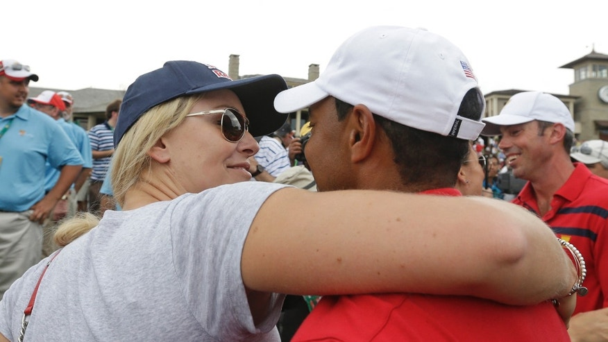 United States team player Tiger Woods is hugged by girlfriend Lindsey Vonn ollowing a four-ball match at the Presidents Cup golf tournament at Muirfield Village Golf Club Saturday, Oct. 5, 2013, in Dublin, Ohio. Woods and Matt Kuchar won 1-up against the International team's Hideki Matsuyama, of Japan, and Adam Scott, of Australia. (AP Photo/Darron Cummings)