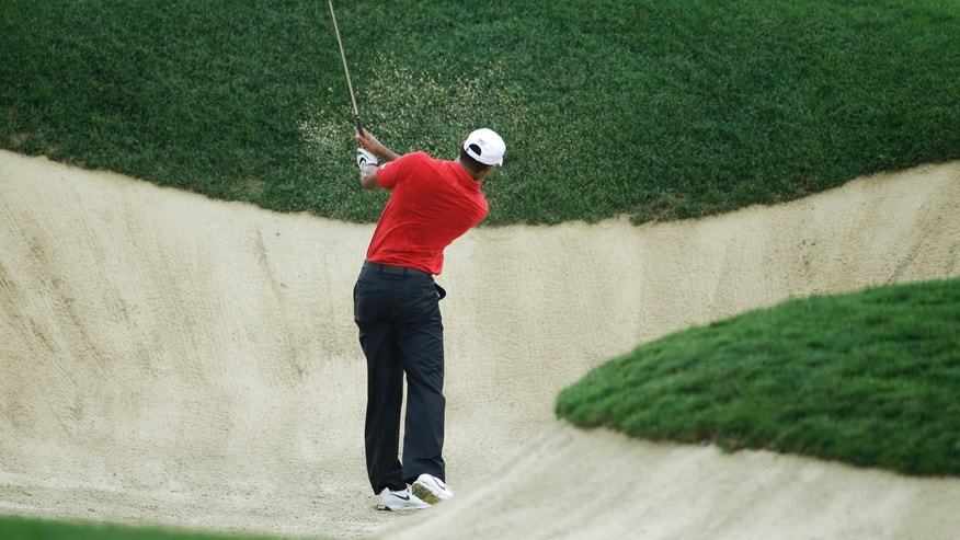 United States' Tiger Woods hits out of a bunker on the 10th hole during the four-ball matches at the Presidents Cup golf tournament at Muirfield Village Golf Club Saturday, Oct. 5, 2013, in Dublin, Ohio. (AP Photo/Darron Cummings)