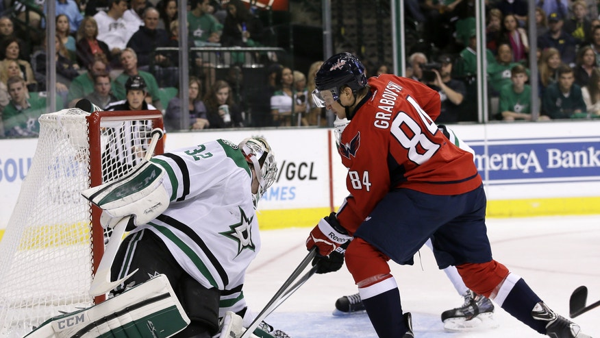 Dallas Stars' Kari Lehtonen (32), of Finland, searches for the puck behind him as Washington Capitals' Mikhail Grabovski (84) pressures in the second period of an NHL hockey game on Saturday, Oct. 5, 2013, in Dallas. Lehtonen was able to gain control of the puck on the play. (AP Photo/Tony Gutierrez)