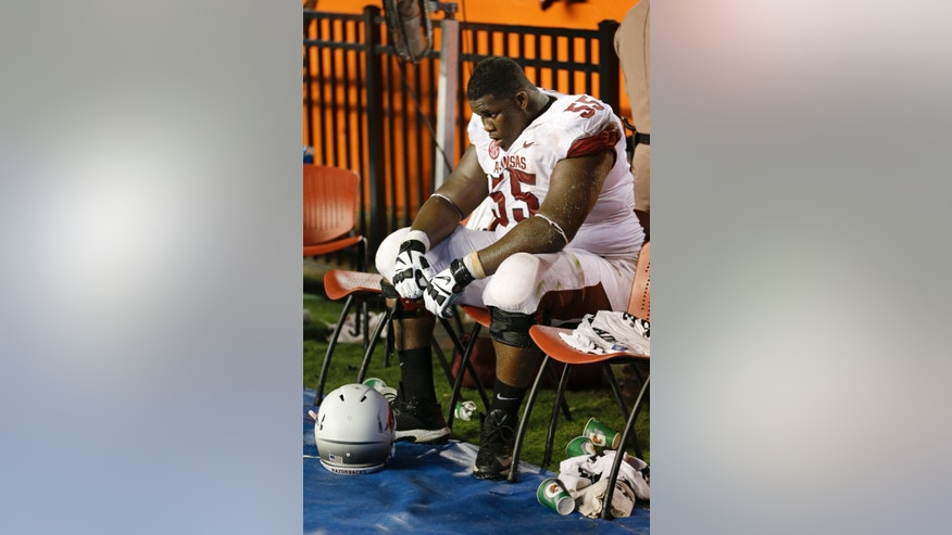 Arkansas defensive tackle Denver Kirkland sits on the bench during the final moments of an NCAA college football game against Florida in Gainesville, Fla., Saturday, Oct. 5, 2013. Florida defeated Arkansas 30-10. (AP Photo/John Raoux)