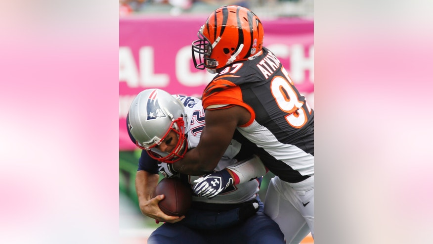 New England Patriots quarterback Tom Brady (12) is sacked by Cincinnati Bengals defensive tackle Geno Atkins (97) in the first half of an NFL football game on Sunday, Oct. 6, 2013, in Cincinnati. (AP Photo/David Kohl)