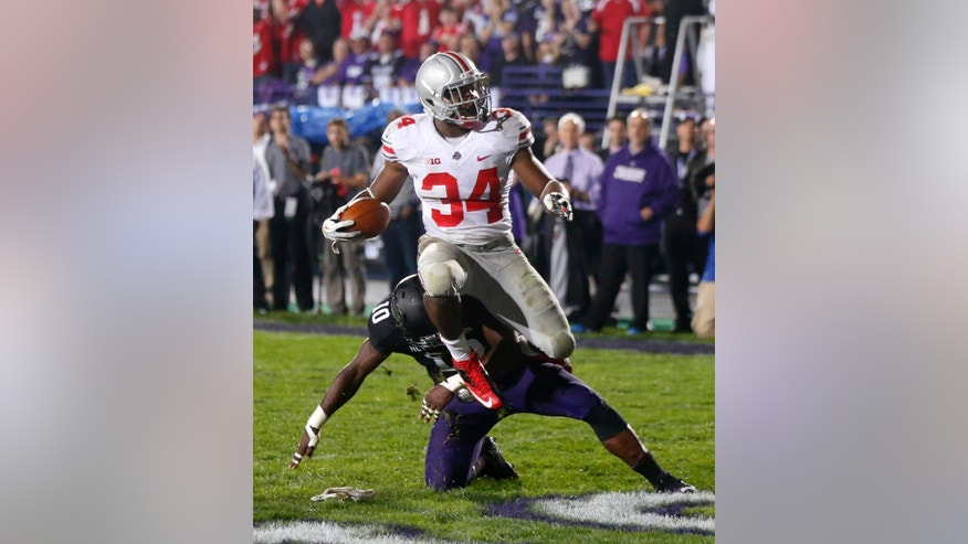 Ohio State running back Carlos Hyde (34) scores over Northwestern safety Traveon Henry during the second half of an NCAA football game Saturday, Oct. 5, 2013, in Evanston, Ill. Ohio State won 40-30. (AP Photo/Charles Rex Arbogast)