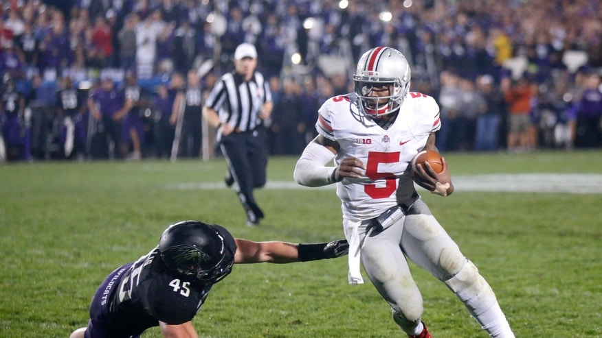 Ohio State quarterback Braxton Miller (5) runs past the outstretched hand of Northwestern linebacker Collin Ellis (45) during the second half of an NCAA college football game Saturday, Oct. 5, 2013, in Evanston, Ill. Ohio State won 40-30. (AP Photo/Charles Rex Arbogast)