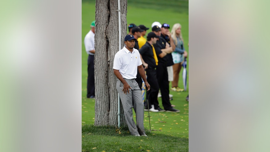 United States team player Tiger Woods rests against a tree on the 18th hole during the single matches at the Presidents Cup golf tournament at Muirfield Village Golf Club Sunday, Oct. 6, 2013, in Dublin, Ohio. (AP Photo/Darron Cummings)