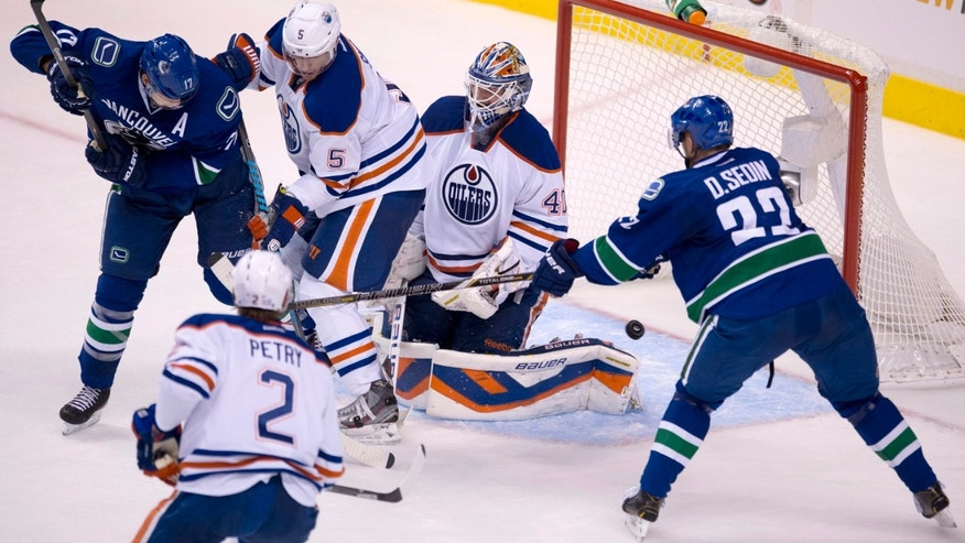 Vancouver Canucks left wing Daniel Sedin (22) puts a shot past Edmonton Oilers goalie Devan Dubnyk (40) as Vancouver Canucks center Ryan Kesler (17), Edmonton Oilers defenseman Jeff Petry (2) and Edmonton Oilers defenseman Ladislav Smid (5) look on during the second period of NHL hockey action in Vancouver, British Columbia, Saturday, Oct. 5, 2013. (AP Photo/The Canadian Press, Jonathan Hayward)