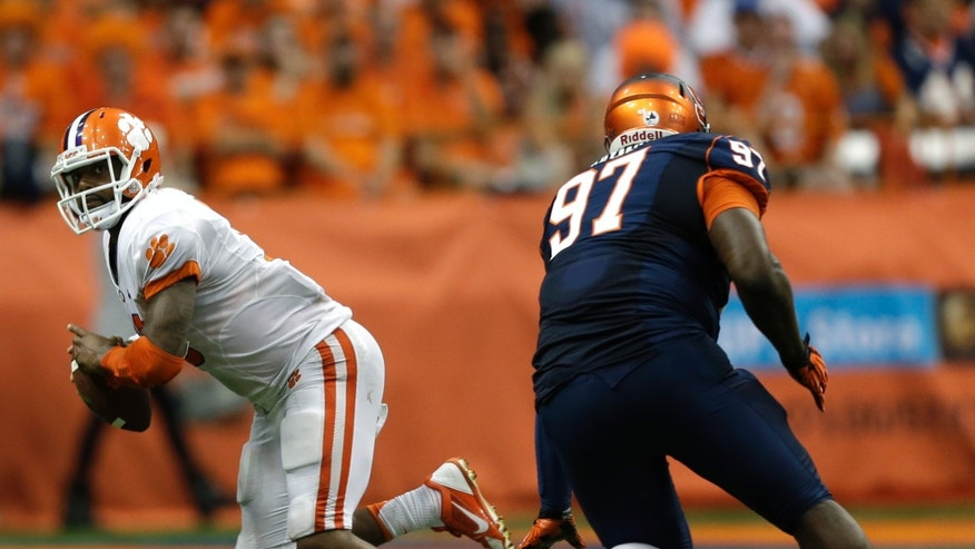 Clemson quarterback Tajh Boyd (10) runs from Syracuse defensive end John Raymon (97) during the second half of an NCAA college football game on Saturday, Oct. 5, 2013, in Syracuse, N.Y. Clemson won, 49-14. (AP Photo/Mike Groll)