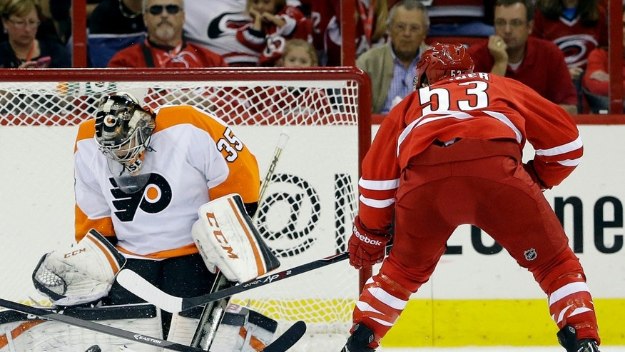 Philadelphia Flyers goalie Steve Mason (35) deflects a shot on goal by Carolina Hurricanes' Jeff Skinner (53)during the first period of an NHL hockey game in Raleigh, N.C., Sunday, Oct. 6, 2013. (AP Photo/Gerry Broome)