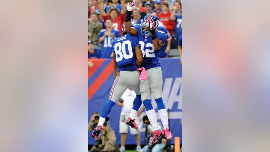 New York Giants' Rueben Randle (82) celebrates with teammate Victor Cruz (80) after scoring a touchdown during the second half of an NFL football game against the Philadelphia Eagles Sunday, Oct. 6, 2013, in East Rutherford, N.J.  (AP Photo/Bill Kostroun)